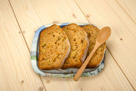 fruitcake: Three slices of homemade fruitcake and a wooden spoon on a tin tray Stock Photo