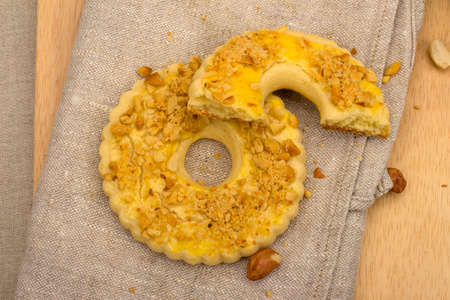 sweetstuff: Round homemade cake with crushed peanuts on gray linen napkin, top view Stock Photo