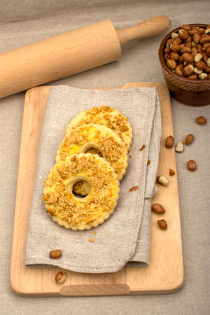 flavored: Three homemade cakes with crushed peanuts on gray linen napkins, wooden rolling pin and a bowl of peanuts in the background, top view Stock Photo