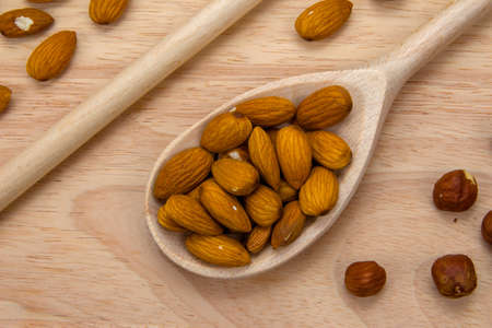 unpeeled: Wooden spoon with unpeeled almonds and hazelnuts on a light wooden board, top view