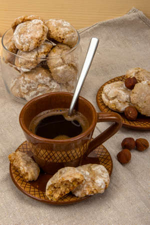 sweetstuff: Amaretti, coffee cup, ceramic saucer with cookies on a gray linen napkins