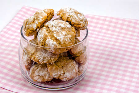 sweetstuff: Italian almond-flavored cookies in transparent glass jar on checkered napkin, close-up