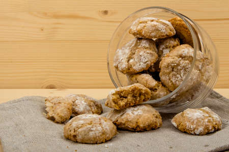 sweetstuff: Transparent glass jar with Italian almond-flavored cookies amaretti dropped out on gray linen cloth on a wooden table Stock Photo