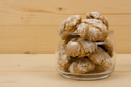flavored: Italian almond-flavored cookies amaretti in transparent glass jar on wooden table, front view right position
