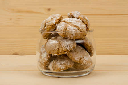 sweetstuff: Italian almond-flavored cookies amaretti in transparent glass jar on wooden table, front view Stock Photo