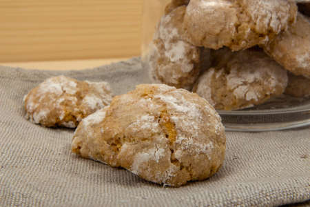 sweetstuff: Italian almond-flavored cookies amaretti close up on the gray linen napkin on wooden table, front view Stock Photo