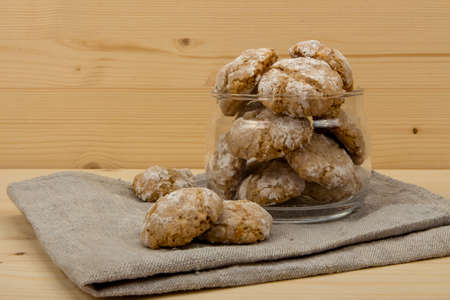 sweetstuff: Italian almond-flavored cookies amaretti in transparent glass jar on the gray linen napkin on wooden table, front view