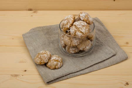 flavored: Italian almond-flavored cookies amaretti in transparent glass jar on the gray linen napkin on wooden table, front view