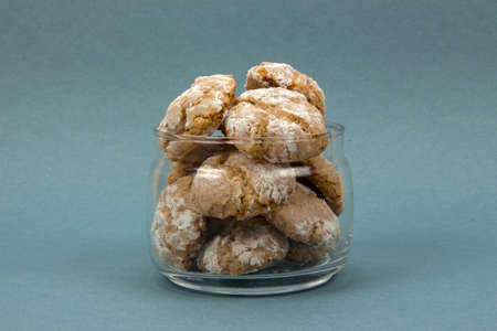 center position: Homemade almond-flavored cookies amaretti in transparent glass jar on a blue background, front view center position