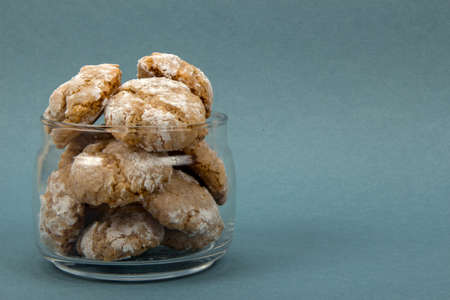 sweetstuff: Homemade almond-flavored cookies amaretti in transparent glass jar on a blue background, front view left position Stock Photo