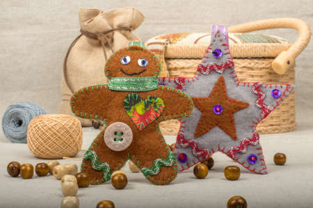basket embroidery: Handmade gray Christmas star and toy gingerbread man of felt gray linen table cloth with jute bags and boxes for needlework in the background Stock Photo