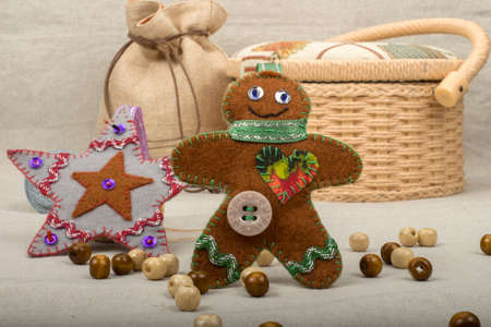 basket embroidery: Handmade toy gingerbread man and a gray star Christmas tree with felt on gray linen table cloth with jute bags and boxes for needlework in the background
