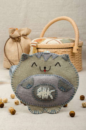 bead embroidery: Toy handmade gray cat from felt with a fish in his stomach on a gray background, front view close-up Stock Photo