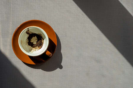 coffee grounds: Empty brown ceramic cup with coffee grounds on a saucer on a gray background with shadows