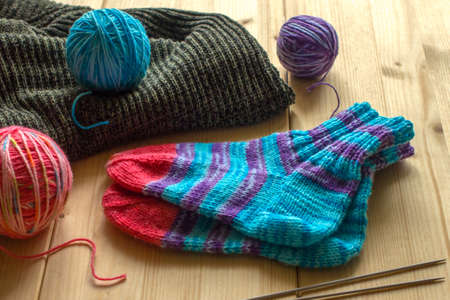 Handmade knitted baby socks, three different colored skeins of wool and two knitting needles on light wooden boards