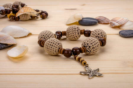 Handmade bracelet crochet beads with pendant starfish on a wooden table with sea pebbles, close-up