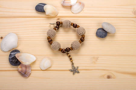 Handmade bracelet crochet beads with pendant starfish on a wooden table with a sea pebbles
