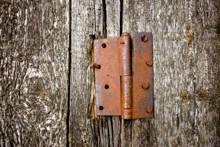 Rusty door hinge on the wooden boards of the old barn, front veiw close-up Stock Photo