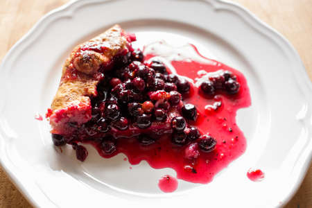 sweetstuff: Homemade pie with fresh black currant and berry sauce on a white plate on a wooden table, top view