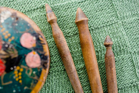 Handmade wooden older spindles on a green hand-knitted coverlet, top view Stock Photo