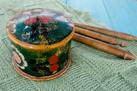 Older wooden round painted casket and three older handmade wooden spindles and an on a green hand-knitted coverlet, front view