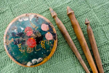 Three older handmade wooden spindles and painted casket on a green hand-knitted coverlet, top view