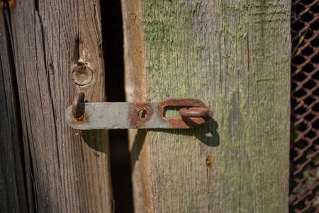 Rusty iron door bolt in an old wooden house of unpainted boards, front view close up