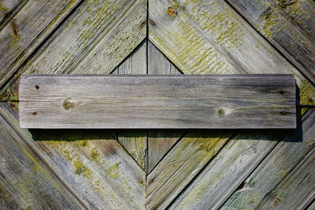 Board nailed to the wall of an old wooden house, peeling green paint, front view close up