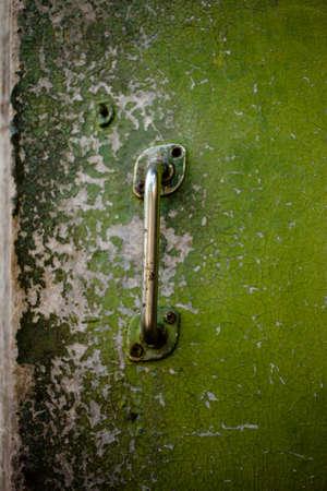 Old shabby green wooden door with a metal door knob, front view