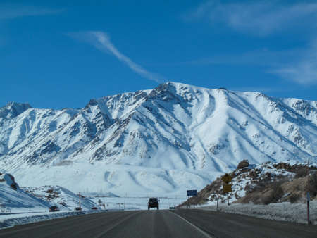 snow covered mountain: An SUV traveling towards a big snow covered mountain