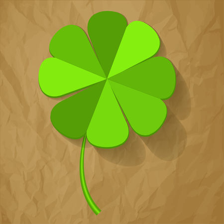 four objects: Four Leaf Clover on a crumpled paper brown background.