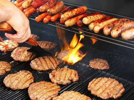 grill: Enjoying a staycation preparing hamburgers and hot dogs  Stock Photo