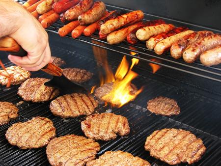 Genießen Sie einen Urlaub auf Balkonien Vorbereitung Hamburgern und Hot Dogs Standard-Bild - 26311263
