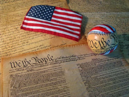 A copy of the Constitution of the United States accompanied by a flag and a baseball with the words of the Constitution on it.
