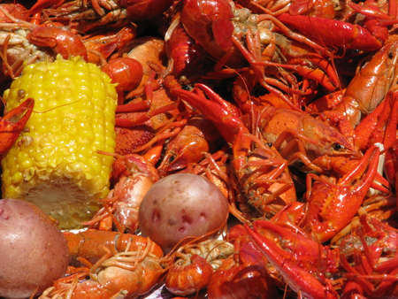 Crawfish potatoes, and corn cob spread out on table.