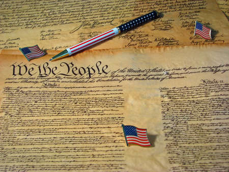A copy of the Constitution of the United States resting on a copy of the Declaration of Independence accompanied by flags and a flag pen.