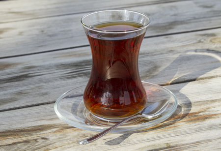 mid afternoon: Traditional turkish glass of tea on the old wooden table