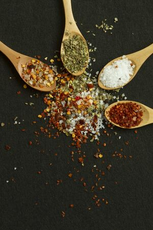 black backgound: Four spoons with different spices and salt on black backgound Stock Photo