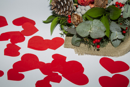 Red hearts from paper in chaotic order and bouquet of flowers on white background