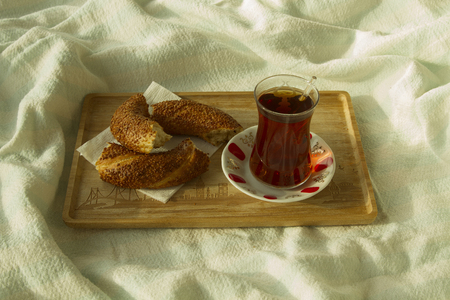 bedcover: Bagel and cup of turkish tea on the wood tray with Istanbul picture on the bedcover, breakfast in bed