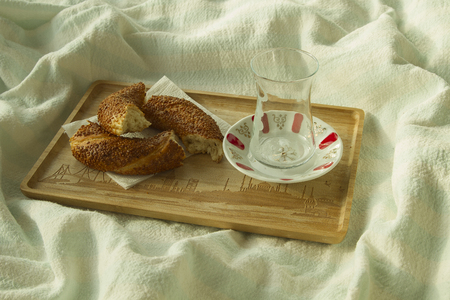 bedcover: Bagel and empty cup for turkish tea on the wood tray with Istanbul picture on the bedcover, breakfast in bed