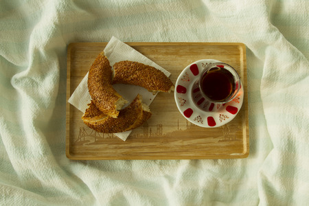 bedcover: Bagel and cup of turkish tea on the wood tray with Istanbul picture on the bedcover, tod down view Stock Photo