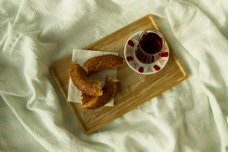 Bagel and cup of turkish tea on the wood tray with Istanbul picture on the bedcover, top down view