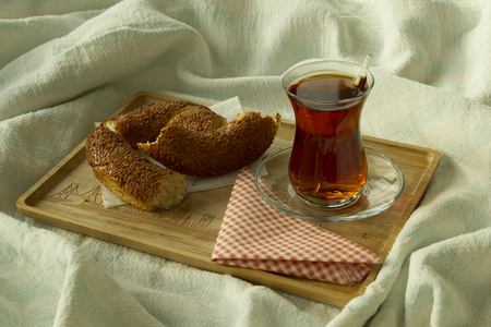 bedcover: Morning turkish tea in traditional glass with bagel on the tray with red napkin, breakfast in bed Stock Photo