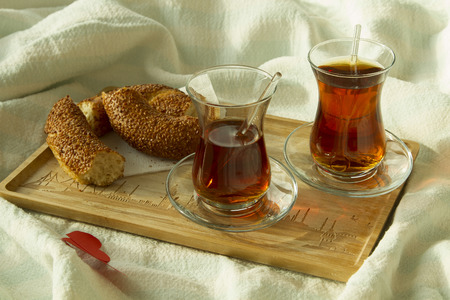 Morning turkish tea in traditional glass with bagel on the tray
