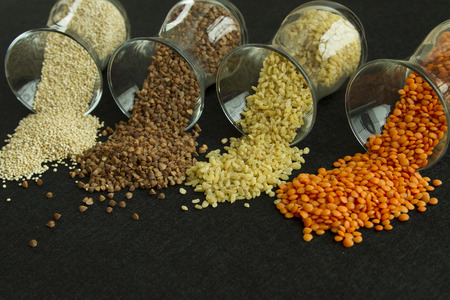Four different groats: buckwheat, lentil, quinoa, bulgur, in transparent glasses on black background