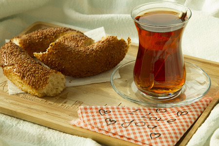 Turkish tea in traditional glass with bagel on the tray with words i love you written on napkin