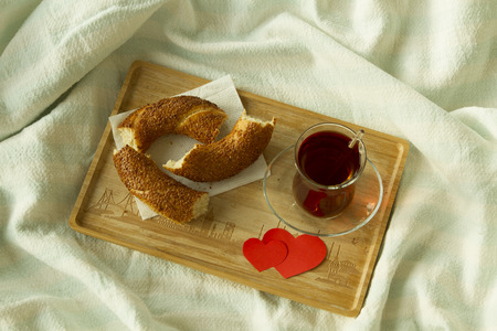 Morning turkish tea in traditional glass with bagel on the tray, breakfast in bed