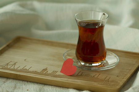 Morning turkish tea in traditional glass with red paper heart, breakfast in bed