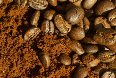 bakground: Coffee beans and ground coffee, horizontal view bakground, extreme macro close up
